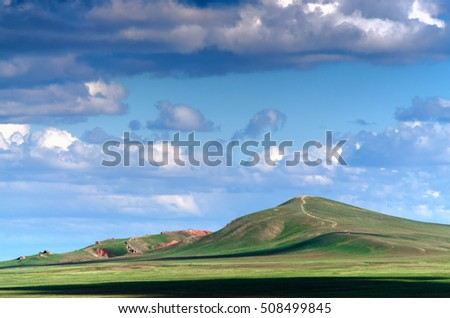 The Bogdo mountain under beautiful sky shoot in May. Spring is beautiful time. Hills are green and covered by emerald grass. Panorama of steppe near salt lake Baskunchak, Russia