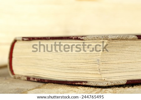 The book is closed and lies on a rough boards  - stock photo