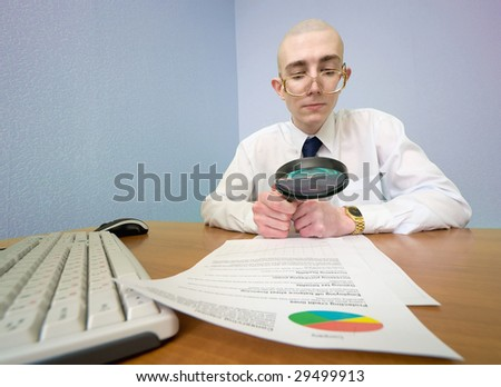 The boss with a magnifier in a hand on a workplace - stock photo