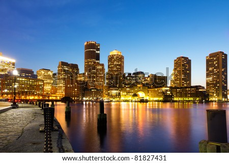 The Boston Harbor and Financial District in Massachusetts, USA at sunset.