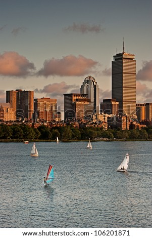 The Boston skyline is illuminated by the setting sun with sailboats in the foreground - stock photo