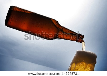 The bottle of levitating beer with glass on desk - stock photo