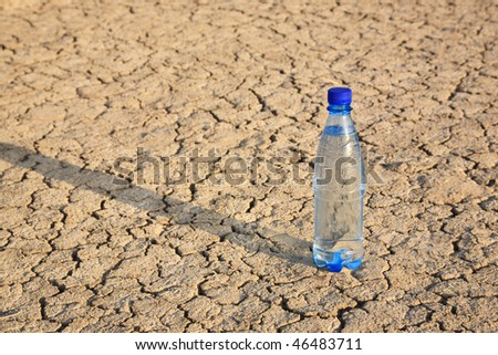 The bottle with cold water with a shadow on the dry cracked ground - stock photo