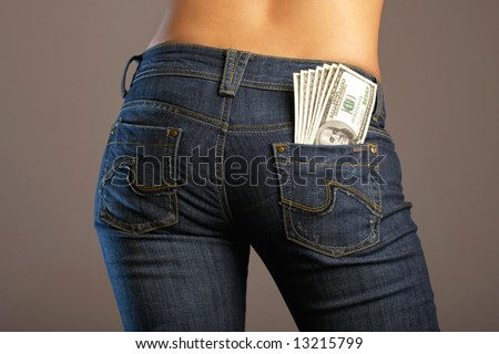 The bottom part of a body of the girl in jeans with a 100 dollar banknotes in a pocket - stock photo