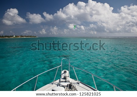 The bow of a dive boat heads out through clear, shallow water towards a dive site in Grand Cayman.  This island in the Caribbean is known for its excellent scuba diving. - stock photo