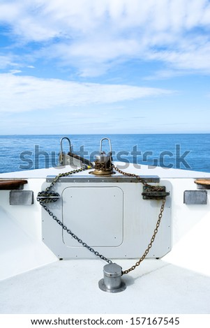 The bow of a passenger cruise boat shows its rusty anchor chain, cleats and winch amongst a blue sky and distant islands. - stock photo