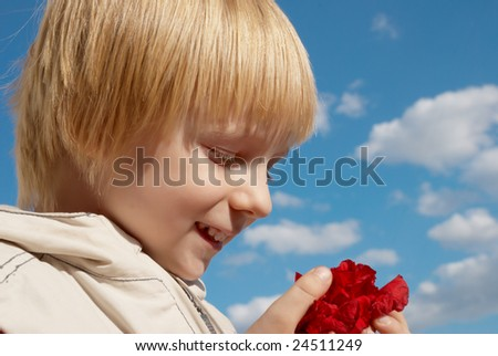 The boy about a red flower in hands - stock photo