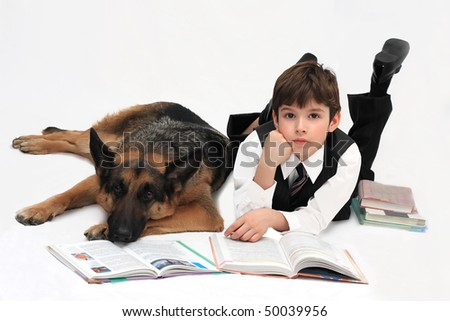 The boy and dog lie on a floor and read books - stock photo