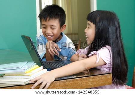 The boy and girl do homework on  laptop