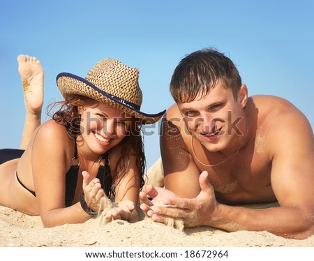 The boy and girl lay on sand - stock photo