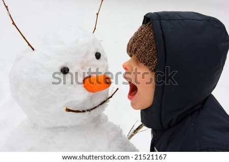 The boy and his snowman - stock photo