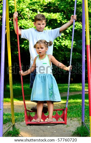 The boy and the girl on a swing in park - stock photo
