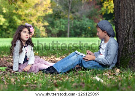 The boy and the girl sit on a grass in park. The boy has a notebook and a pencil in his hands