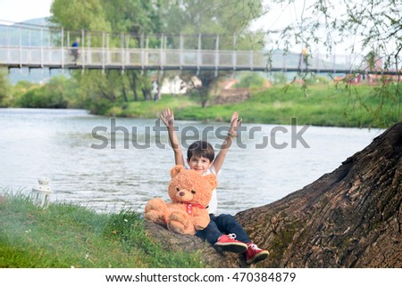 The boy and the teddy bear by the river