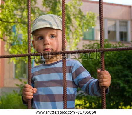 The boy behind a lattice - stock photo