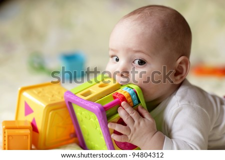 The boy biting a toy on a bed at home - stock photo