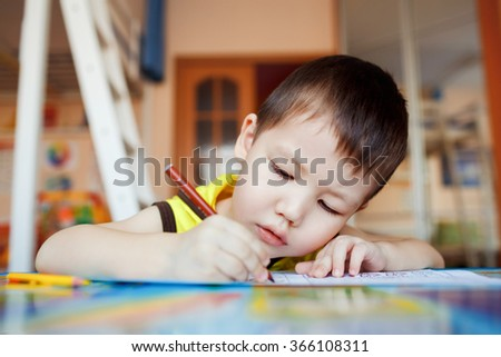 The boy carefully and intently draws in a special notebook for drawing, education at home, pre-school training, the development of creative abilities of children. Classroom in the house. - stock photo