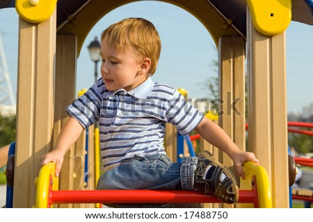 The boy climb on the equipment of a playground - stock photo