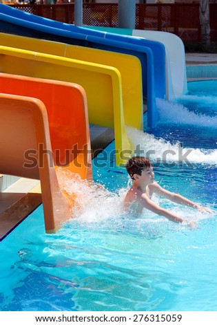 The boy coming down the slide in aqua park - stock photo