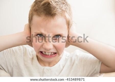 The boy covers his ears. Stress - stock photo
