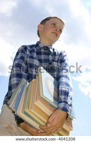 The boy drags a pile of heavy books