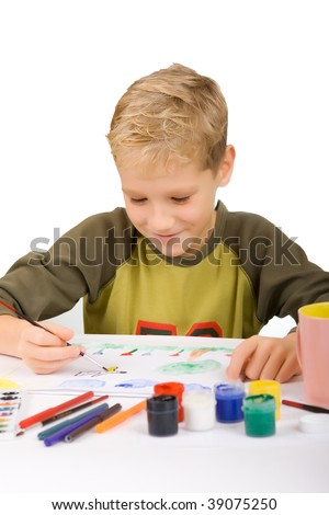 The boy draws gouache on sheet of a white paper