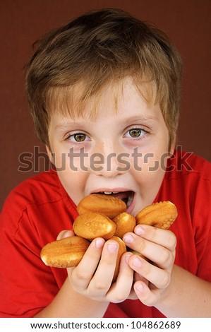The boy eating tasty cakes - stock photo