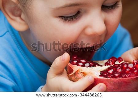 The boy eats a pomegranate - stock photo