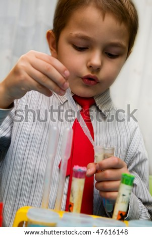 The boy enthusiastically studying chemistry and makes his first experience in chemical - stock photo