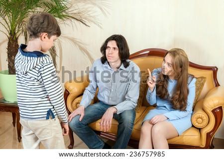 the boy explains his behavior to parents - stock photo