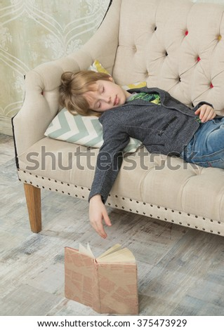 The boy fell asleep and dropped the book - stock photo