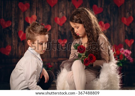 The boy gives a gift to the girl.    - stock photo