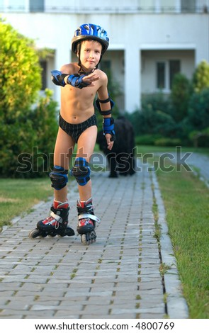 The boy goes for a drive on roller skates sidewalk - stock photo