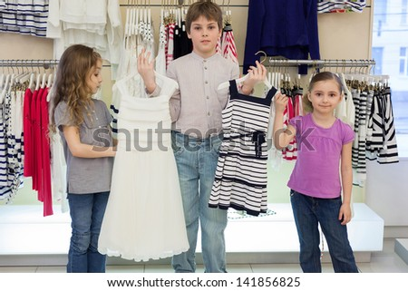 The boy helps cute girls to choose dress in shop of childrens clothing - stock photo