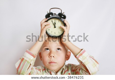 The boy holds an alarm clock on a head. - stock photo