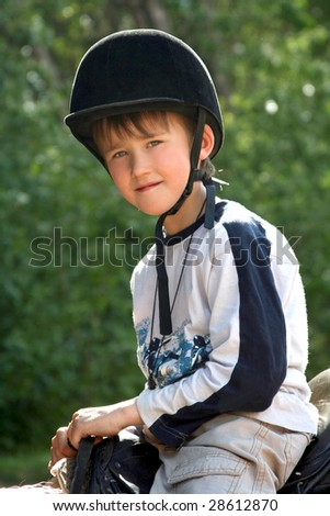 The boy in a cap of the equestrian on a background of greens