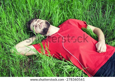 The boy in a green grass listens to music - stock photo