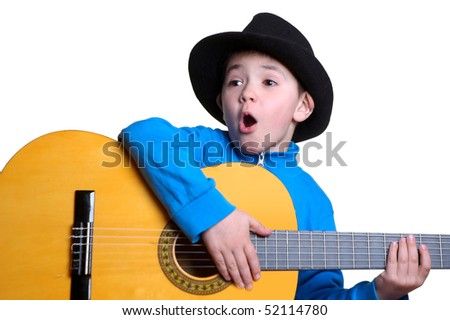 The boy in a hat plays a guitar - stock photo