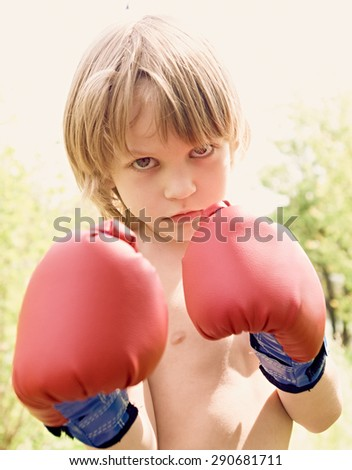 The boy in boxing gloves against a light background, close up portrait