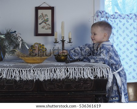 The boy in Russian national costume at the Christmas table / boy playing with Christmas candles