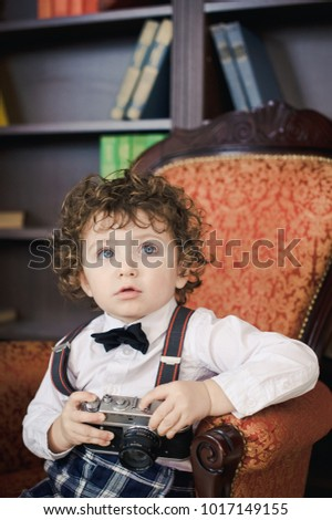 The boy in the armchair in the library. Curly little boy with old camera