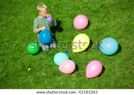 The boy inflates balloons, sitting on a grass - stock photo