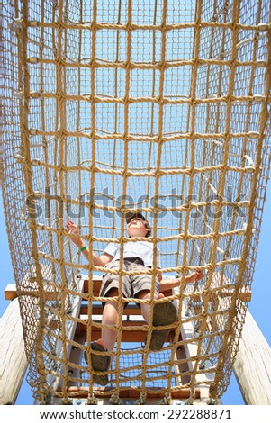 The boy inside the cable cell in playground, bottom view - stock photo