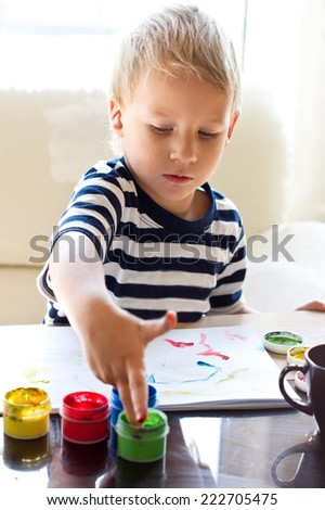 The boy is painting with fingers paints - stock photo