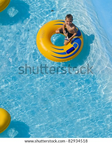 The boy is riding on an inflatable donut at a water park - stock photo