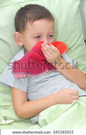 The boy is sick. Lies in pastels and blowing his nose - stock photo