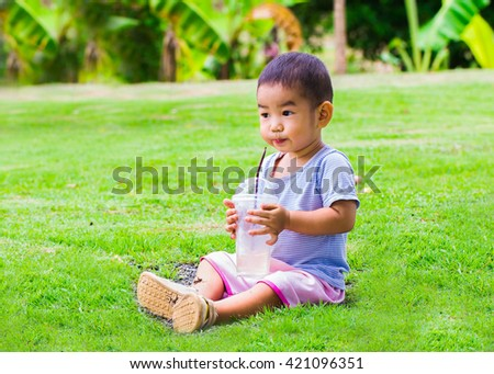The boy is sucking water with straws in a glass with ice. water with straws - stock photo