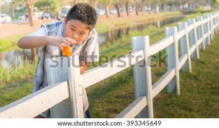 The boy is trying to put the ball on a white fence - stock photo