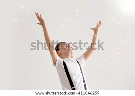The boy joyfully plays with soap bubbles - stock photo