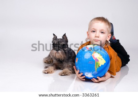 The boy lays with the globe and a dog on a white background - stock photo